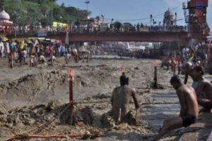 A Hindu devotee tries to take a holy dip in the flooded Ganges river in Haridwar