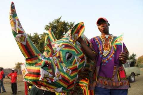 Paricipants of the Victoria Falls street Carnival stand next to a Rhino dressed in Zimbabwean colours
