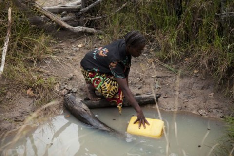 Dimitria Lubinga collecting water from an unsafe open well that is 20 minutes walk from her house, Habeenzu village, Zambia