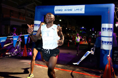 Harry Mulenga crosses the finish line to win the KPMG Front Street Mile. *Photo by Nicola Muirhead.