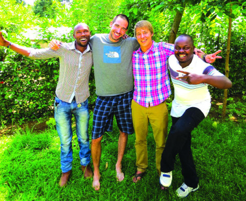 Jordan Edgcomb, center left, and Josh Dube, center right, pose with safari guides Noeli, left, and Douglas, right, during their months-long foray through Africa in late 2013