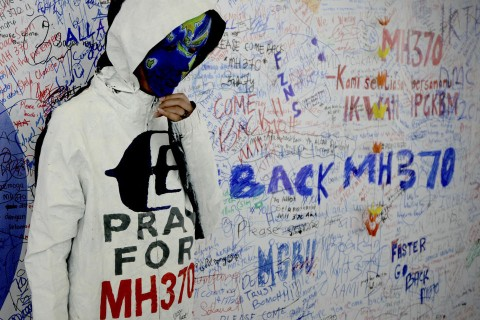 An unidentified woman with her face painted, depicting the flight of the missing Malaysia Airline, MH370