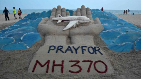 Beachgoers walk past a sand sculpture made by Indian sand artist Sudersan Pattnaik with a message of prayers for the missing Malaysian Airlines Flight MH370 at Puri beach in India March 12, 2014