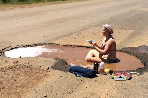 Female teacher strips off to take BATH in pothole for protest on road conditions