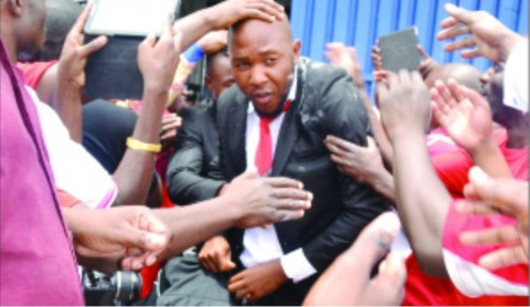 NKANA defender, Christopher Munthali swarmed by fans on arrival at Simon Mwansa Kapwepwe International Airport in Ndola yesterday. Picture by FELIX MALUNGA