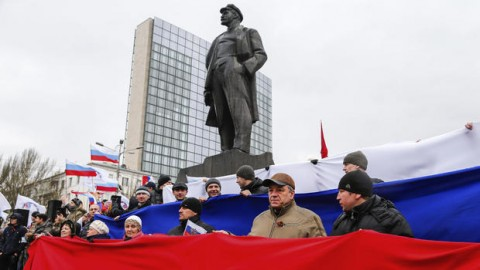 Pro-Russia demonstrators form a Russian flag as they stand under a statue of Soviet revolutionary leader Vladimir Lenin during a rally in Donetsk, Ukraine, Sunday, March 16, 2014. ANDREY BASEVICH, AP
