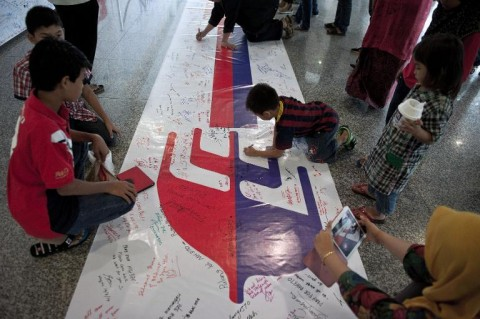 Visitors write on a banner carrying messages for the passengers of missing Malaysia Airlines flight MH370 at Kuala Lumpur International Airport (KLIA) in Sepang, outside Kuala Lumpur
