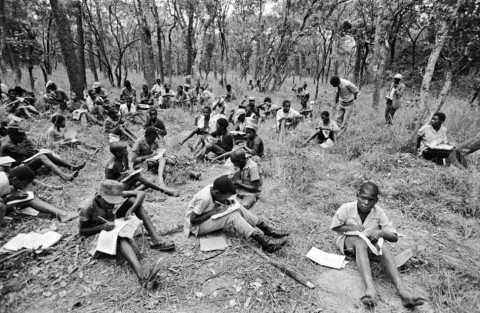 For lack of a school building, the inmates of the Solwezi camp for boys attend lessons in the nearby forest, Zambia, 1979