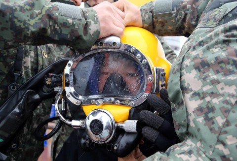 A diver wears a helmet to look for people still missing from the sunken ferry Sewol, in the water off the southern coast near Jindo, South Korea, Saturday, April 26, 2014