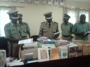 Commissioner of Prisons Percy Chato (centre) with some members of the Prisons Command. looking at the books donated from Canada