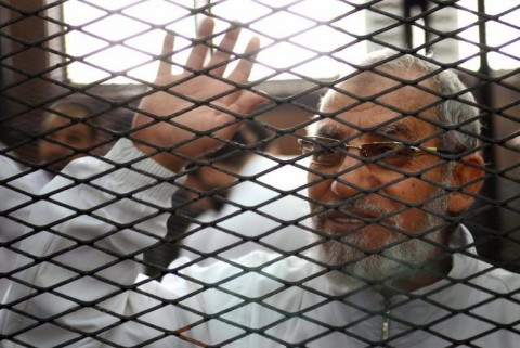 Egyptian Muslim Brotherhood leader Mohamed Badie waves from inside the defendants cage during the trial of Brotherhood members on February 3, 2014 near Cairo's Turah prison (AFP Photo/Ahmed Gamil)