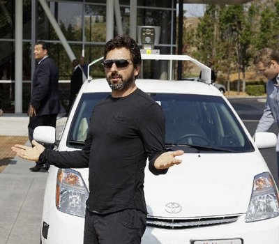 Google co-founder Sergey Brin gestures after riding in a driverless car in 2012. Google reports making big gains in creating a car that can drive itself but caution that commercially available cars remain years away
