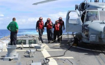 Sailors inspecting the flight deck of the Arleigh Burke-class destroyer USS Kidd (DDG 100) at sea in the Indian Ocean on March 16, while conducting search and rescue (SAR) operations for the missing Malaysian Airlines flight MH370