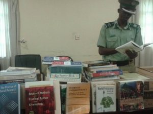 The Commander Training College Kapalu Luneta perusing through the book donation from Canada that was handed over to his institution.
