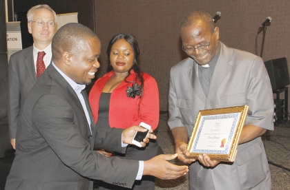 ZAMBIA Daily Mail news editor Newton Sibanda reaches out for his certificate from Archbishop of Lusaka Telesphore Mpundu during the 2014 Media Institute of Southern Africa (MISA) Zambia media awards