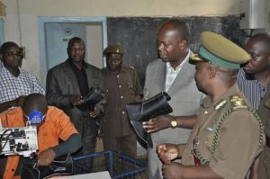 ZAMBIA PRISONS SERVICE COMMISSIONER PERCY CHATO ADMIRING PART OF A BOOT MADE BY INMATES AT TANZANIA PRISONS SHOE MAKING WORKSHOP.