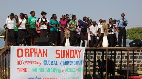 In this 2012 photo provided by the Christian Alliance for Orphans, a pastor, right, speaks on stage accompanied by orphaned children from the Lusaka region