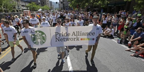 In this June 8, 2014, photo, workers carry a Starbucks banner during the gay pride parade, in Salt Lake City