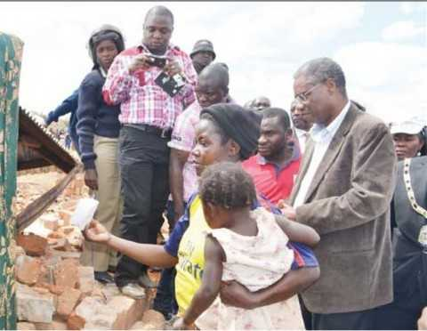 LOCAL Government and Housing Minister Emmanuel Chenda listens to Elizabeth Bwalya explaining the extent of damage to her house in Mindolo North in Kitwe yesterday. Picture By MOFFAT CHAZINGWA