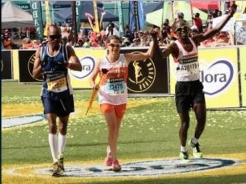 Zola Budd is escorted over the line by Bongani Possa, left, and Ken Mwapa of Zambia after finishing the Comrades Marathon. Photo- Sibonelo Ngcobo