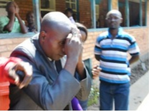 HOLY Fire Christian Ministry Church Bishop Dominic Nyondo shielding his face from cameras at the Kitwe magistrate's court after he appeared for defilement yesterday. Picture by MOFFAT CHAZINGWA.