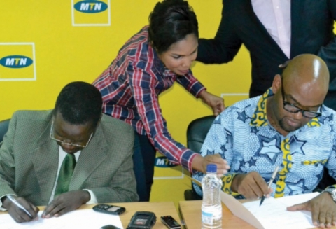 TIMESPRINTPAK Acting Deputy Managing Director Venarcious Mwansa sings an agreement with MTN Zambia chief sales and distribution officer Amon Jere in Lusaka yesterday. Picture by STEPHEN KAPAMBWE.