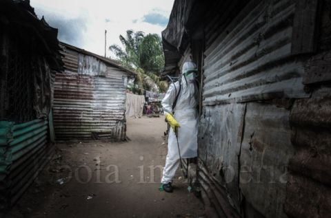 A member of the team enters the home of a victim - Ebola crisis in Liberia
