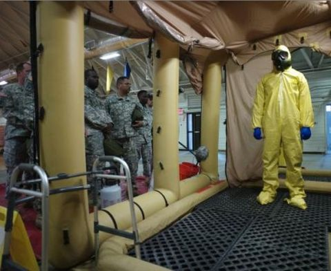 A soldier goes through the decontamination process with U.S. Army soldiers from the 101st Airborne Division (Air Assault), who are earmarked for the fight against Ebola, take part in training before their deployment to West Africa, at Fort Campbell, Kentucky October 9, 2014.