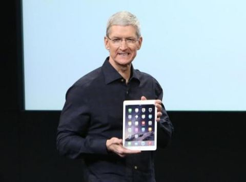 Apple CEO Tim Cook holds an iPad during a presentation at Apple headquarters in Cupertino, California October 16, 2014.