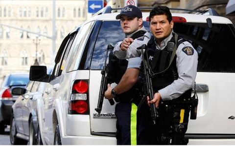 Armed RCMP officers guard access to Parliament Hill following a shooting incident in Ottawa, Canada, October 22, 2014.