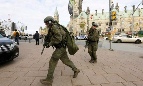 Armed RCMP officers head towards the Langevin Block on Parliament Hill. Photograph- Chris Wattie:Reuters