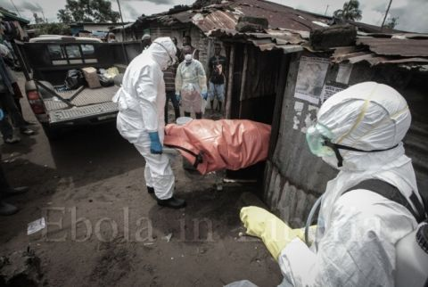 Dressed in protective clothing, Garmai Sumo and his colleagues carry the body of 40-year-old Mary Nyanforh from her house - Ebola crisis in Liberia