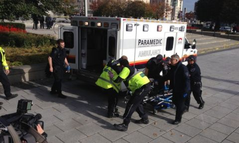 Police and paramedics transport a wounded soldier after a shooting at the war memorial. Photograph- Michael Comte:AFP:Getty