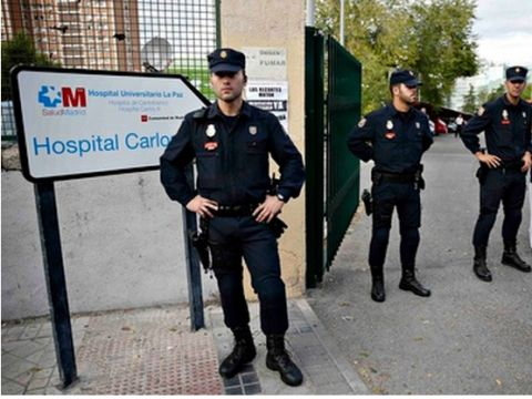 Police stand at the entrance of the Carlos III hospital in Madrid. Photograph: Paul Hanna/Reuters