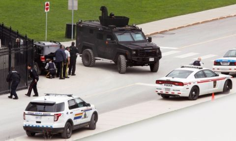 Police take cover near Parliament Hill after the shootings. Photograph- Chris Wattie:Reuters