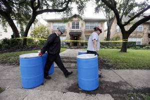 Protect Environmental workers move disposal barrels to a staging area outside the apartment of a hea …