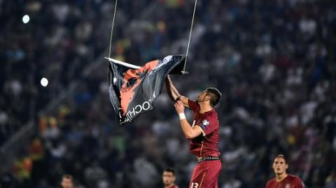 Serbia's Stefan Mitrovic grabs a flag with Albanian national symbols flown by a remotely operated drone during the Euro 2016 group I football match between Serbia and Albania