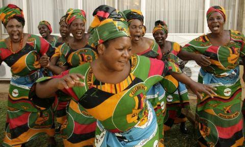 Zambian women sing at Lusaka's international airport in 2008