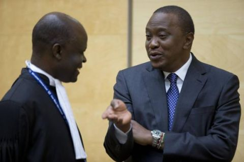 enya's President Uhuru Kenyatta (R) speaks to a member of his defence team as he appears before the International Criminal Court in The Hague October 8, 2014.