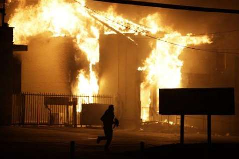A man runs away from the burning storage facility after the announcement of the grand jury decision Monday, Nov. 24, 2014, in Ferguson, Mo