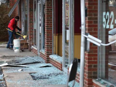 A worker cleans up glass at a building that was damaged during a demonstration on Nov. 25, 2014 in Dellwood, Mo.