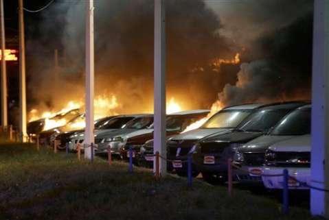 Cars burn at a dealership Tuesday, Nov. 25, 2014, in Dellwood, Mo