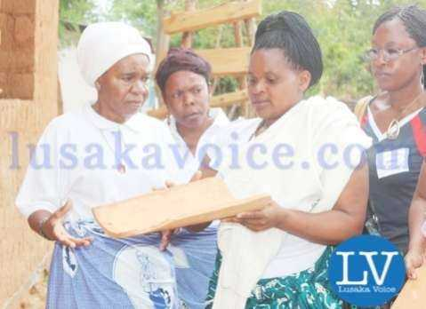 GWRAZ Member Odile Furaha explaining to Chieftainess Nkomesha the process of making a clay soil tile - Lusakavoice.com