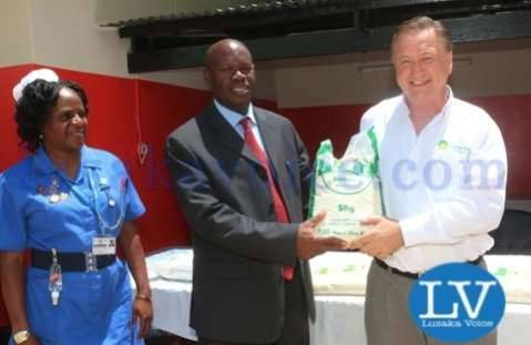 Superior Milling CEO Peter Cottan shaking hands with UTH MD Luckson Kasonka while looking is UTH Maternity ward matron Beatrice Mundia  - Lusakavoice.com