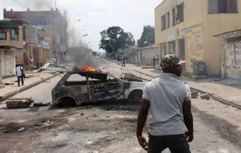 A demonstrator walks near a car set ablaze to barricade a street during a protest in the Democratic Republic of Congo's capital Kinshasa, protests erupted