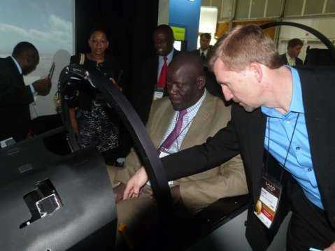 An exhibitor showing Hon Davies Mwila specifications of a Jet Fighter plane