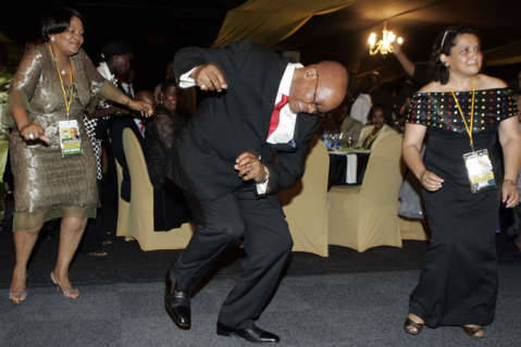 African National Congress president Jacob Zuma, center, with party members dances during the party's Manifesto pre-launch gala dinner in East London