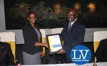 Rotary International District 9210 Governor Kenneth Chibesakunda presenting a certificate to the ECZ Director (Guest of Honour) Isaac Priscilla - Photo Credit Jean Mandela - Lusakavoice.com