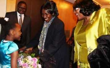 Zambia Vice-President Her Honour Mrs Inonge Wina (second right) receives a bouquet of flowers from eight-year-old Tasheni Bota on arrival at New York Palace Hotel in New York on Sunday, March 8, 2015. Looking on is Zambia's Ambassador to the UN Her Excellency Dr Mwaba Kasese-Bota (right) and Zambia's Ambassador to the US His Excellency Mr. Palan Mulonda. The Vice-President is leading the Zambian delegation to the 59th Session of the Commission on the Status of Women. PHOTO | CHIBAULA D. SILWAMBA | ZAMBIA UN MISSION