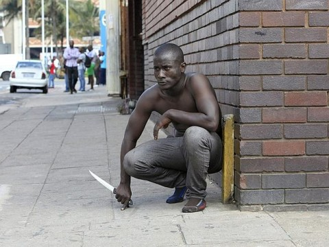 A city in lockdown ... a foreign national holds a knife following clashes between a group